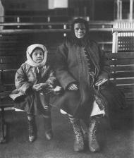 Migrante con su hija en la isla de Ellis a principios del siglo XX.