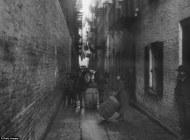 Niños jugando con unos barriles bajo la ropa tendida en un callejón junto a Mulberry Street. / Jacob Riis, 1890.