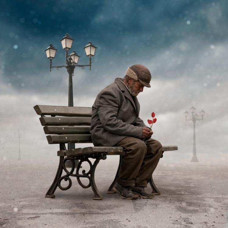 anciano-sentado-banco-abandonado-flor