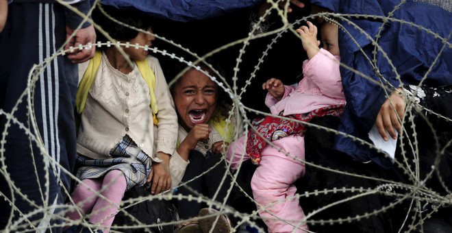 una-nic3b1a-refuegiada-llora-tras-la-alambrada-policial-que-les-impide-cruzar-la-frontera-entre-grecia-y-macedonia-reuters