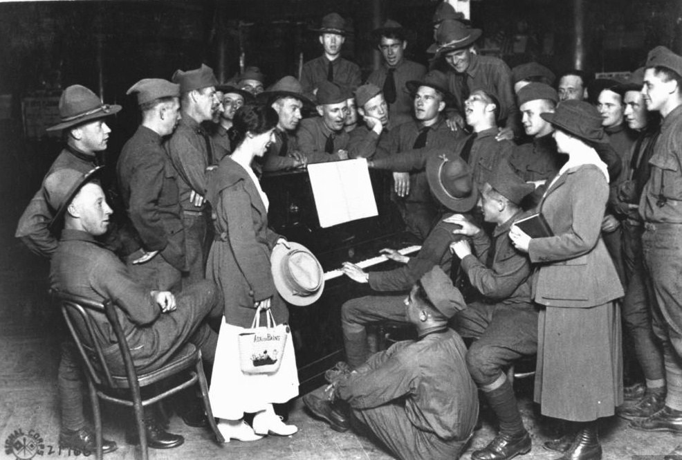 us-soldiers-and-ymca-girls-gathered-around-a-piano-player-and-enjoying-a-sing-along-during-leisure-time-from-wwi-aix-le-bains-france-august-1918
