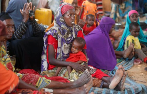 Internally displaced Somali women sit with their children inside their general shelter at the Al-cadaala camp in Somalia's capital Mogadishu